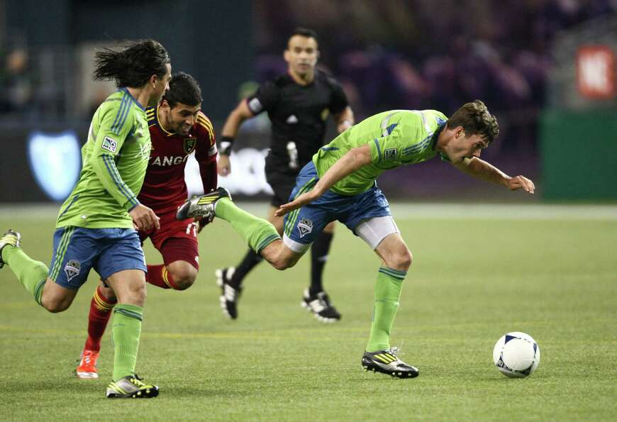 Seattle Sounders player Brad Evans is tripped up by Real Salt Lake player Javier Morales (11) in a p