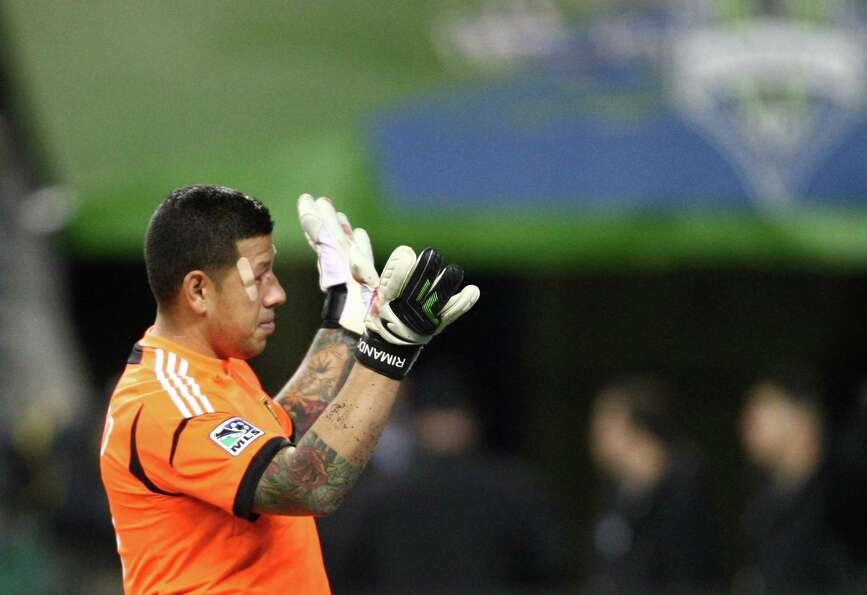 Real Salt Lake goalie Nick Rimando waves to booing Sounders fans after he was kicked in the head dur