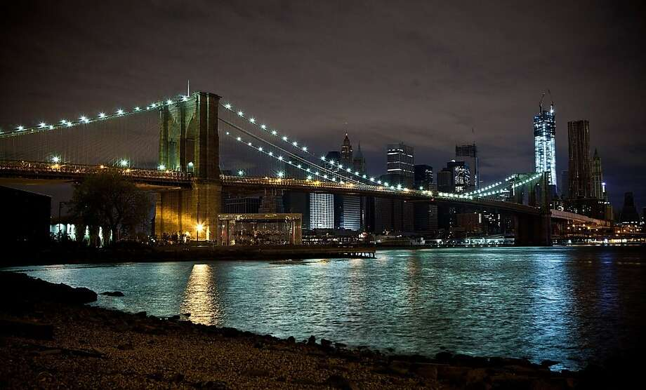 The lights of New York's Financial District neighborhoods are seen next to the Brooklyn Bridge on November 2, 2012 in the Brooklyn borough of New York City. Select neighborhoods of Manhattan are beginning to recover power as Con Edison repairs damage done by Superstorm Sandy. Photo: Andrew Burton, Getty Images