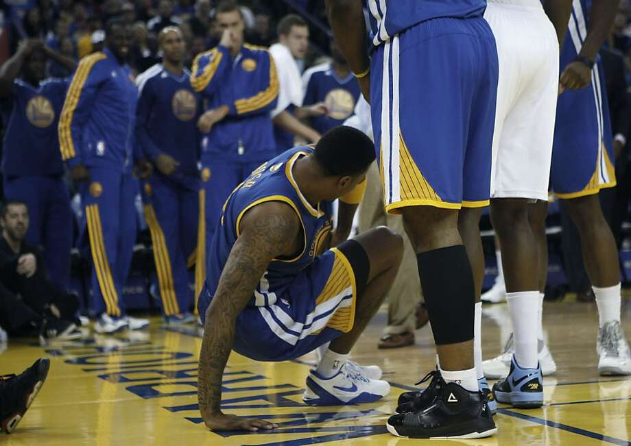 Warriors Brandon Rush tries getting up after hurting his knee during the first half as the team watches at Oracle arena in Oakland, Calif.,  on Friday, November 2, 2012. Photo: Liz Hafalia, The Chronicle