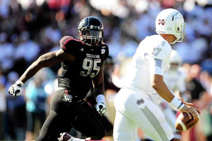 Julien Obioha #95 of the Texas A&M Aggies pursues Tyler Russell #17 of the Mississippi State Bulldog