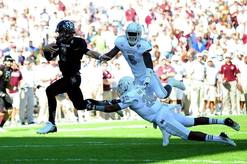 Johnny Manziel #2 of the Texas A&M Aggies runs past Louis Watson #20 of the Mississippi State Bull