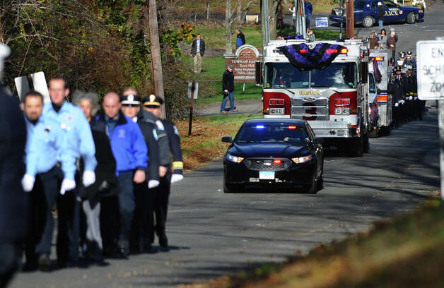 Easton Fire Department firefighters and fire engine #3 lead a procession for the funeral and memorial mass of firefighter Russell Neary at Notre Dame Roman Catholic Church in Easton, Conn. on Saturday November 3, 2012. Neary died when a tree fell on him as he was on duty during Hurricane Sandy this past Monday. Photo: Christian Abraham / Connecticut Post