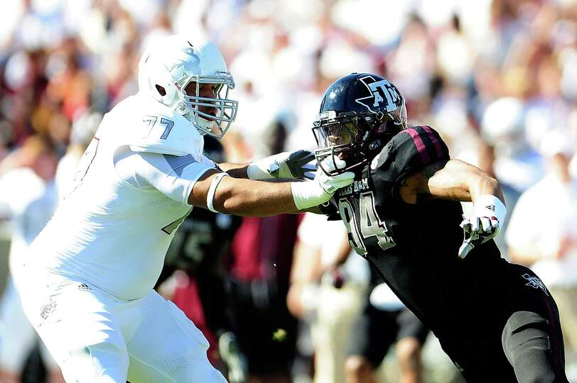 Damontre Moore #94 of the Texas A&M Aggies rushes against Joey Trapp #77 of the Mississippi State