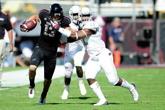 Mike Evans #13 of the Texas A&M Aggies stiff arms Chris Hughes #12 of the Mississippi State Bulldogs. Photo: Stacy Revere, Getty Images / 2012 Getty Images