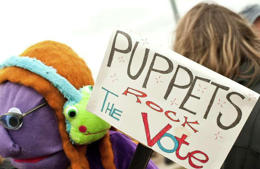 A woman holds a puppet and a sign during the