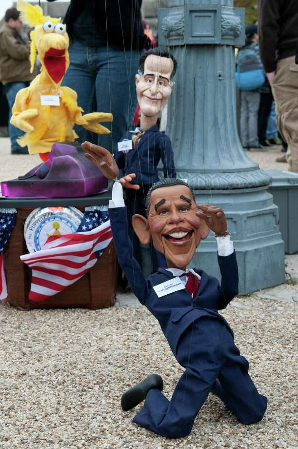 Puppeteers manipulate likenesses of US President Barack Obama and his Republican challenger Mitt Romney during the Million Puppet march in support of public broadcasting in Washington on November 3, 2012. Several hundred supporters of US public broadcasting in a good-humored protest prompted by Romney's threat, in a televised debate with Obama a month ago, to halt government funding to public media if he wins the White House on November 6.    AFP PHOTO/Nicholas KAMMNICHOLAS KAMM/AFP/Getty Images Photo: NICHOLAS KAMM, AFP/Getty Images / AFP
