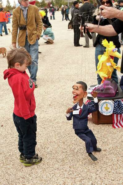 A child watches puppeteer Scott Land manipulate a likeness of US President Barack Obama during the M