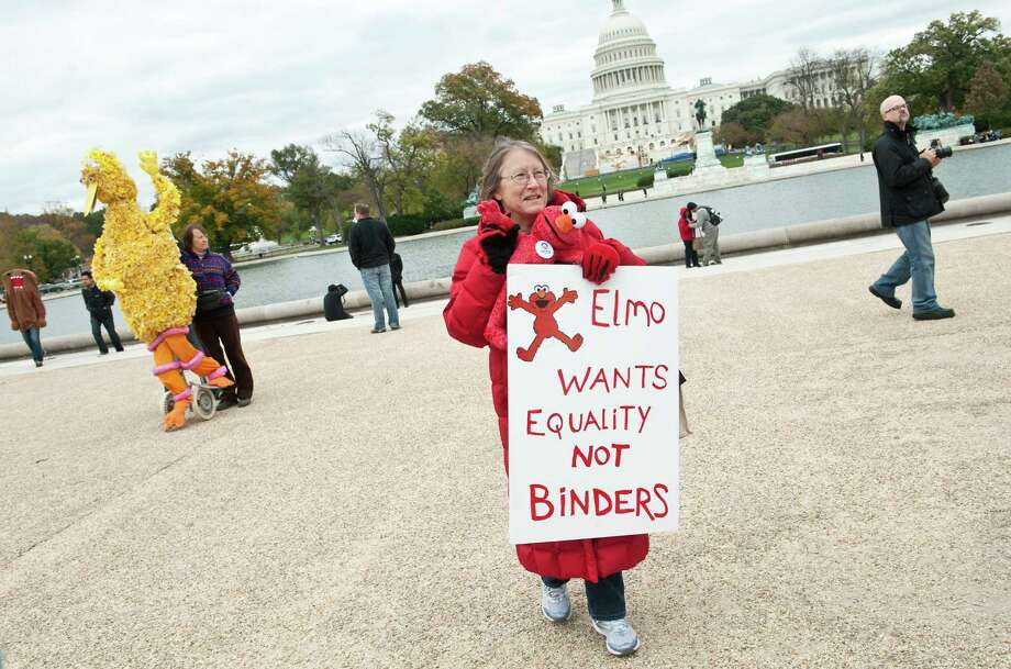 "A woman holds a sign in support of public broadcasting during the ""Million Puppet March"" in Washington on November 3, 2012. Several hundred supporters of US public broadcasting in a good-humored protest prompted by Romney's threat, in a televised debate with Obama a month ago, to halt government funding to public media if he wins the White House on ovember 6.    AFP PHOTO/Nicholas KAMMNICHOLAS KAMM/AFP/Getty Images Photo: NICHOLAS KAMM, AFP/Getty Images / AFP"