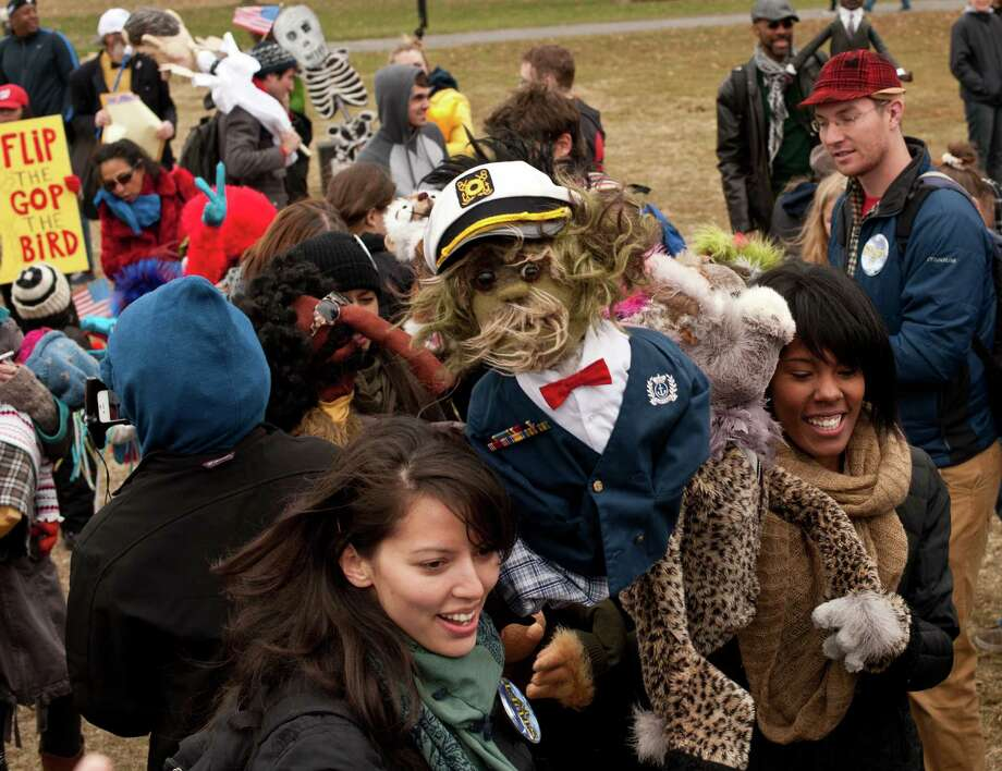 """People dance with puppets in support of public broadcasting during the """"Million Puppet March"""" in Washington on November 3, 2012. Several hundred supporters of US public broadcasting in a good-humored protest prompted by US Republican candidate Mitt Romney's threat, in a televised debate with President Barack Obama a month ago, to halt government funding to public media if he wins the White House on ovember 6.    AFP PHOTO/Nicholas KAMMNICHOLAS KAMM/AFP/Getty Images Photo: NICHOLAS KAMM, AFP/Getty Images / AFP"""