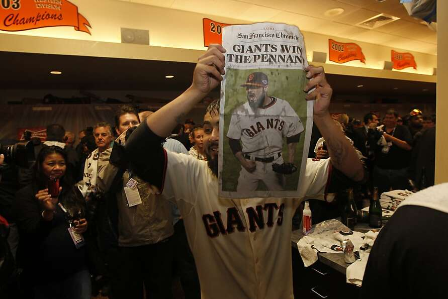 San Francisco  pitcher Sergio Romo displays a newspaper telling of their win  as they celebrate thei