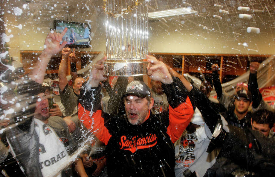 Manager Bruce Bochy hoists the championship trophy after the Giants swept the Tigers in 2012. Photo: Michael Macor / The Chronicle / ONLINE_YES