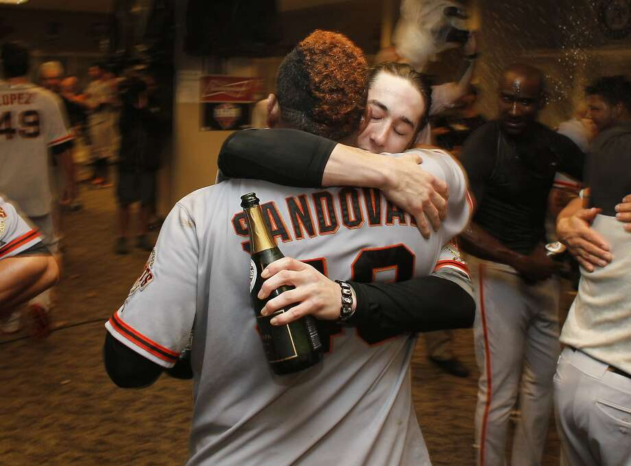 Giants' Pablo Sandoval and Tim Lincecum embrace, while the team celebrates in the clubhouse, as the San Francisco Giants beat the Cincinnati Reds 6-4 in game five to win the National League Division Series in Cincinnati, Ohio on Thursday Oct. 11, 2012. Photo: Michael Macor, The Chronicle