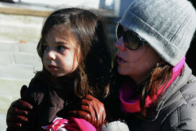 Carrie June, of Easton, and her daughter Josey, 4, watch a funeral and memorial mass which was held for Easton firefighter Russell Neary in front of Notre Dame Roman Catholic Church in Easton, Conn. on Saturday November 3, 2012. Neary died when a tree fell on him as he was on duty during Hurricane Sandy this past Monday. Photo: Christian Abraham / Connecticut Post