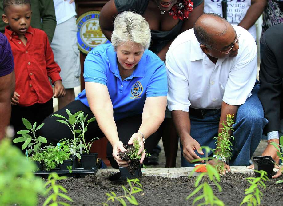 Mayor Annise Parker and Senator Rodney Ellis plant herbs and vegetables at the newly created Harry Holmes Healthy Harvest garden in Sunnyside, Saturday, Nov. 3, 2012, in Houston. Mayor Parker helped to dedicate the community garden at 4646 Brinkley, in Sunnyside.  This is the first project by Urban Harvest's I-Grow Houston initiative, which helps to build  community gardens  on vacant land in areas with poor access to healthy fresh foods. Photo: Karen Warren, Houston Chronicle / © 2012  Houston Chronicle