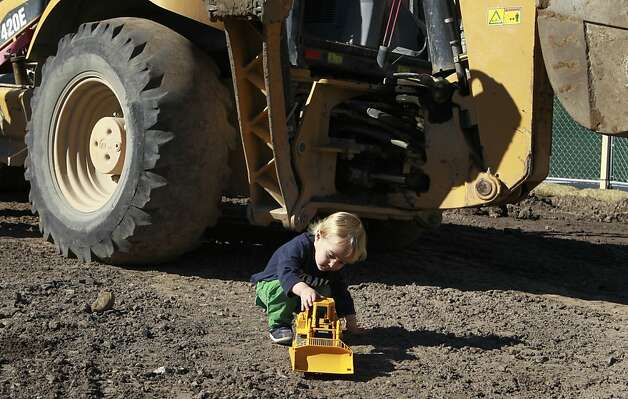 Matthew Smolen plays with toy construction equipment in front of the real thing at the groundbreaking ceremony for the North Beach branch library. Photo: Paul Chinn, The Chronicle