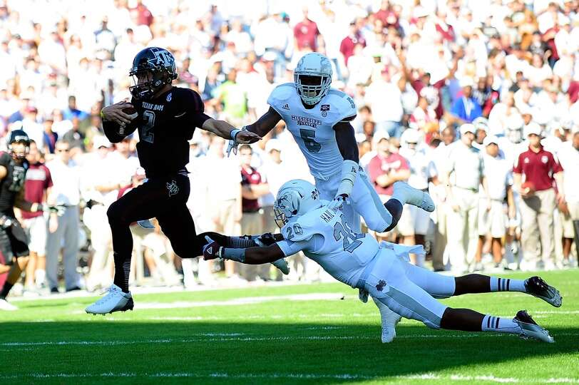 Johnny Manziel #2 of the Texas A&M Aggies runs past Louis Watson #20 of the Mississippi State Bulldo