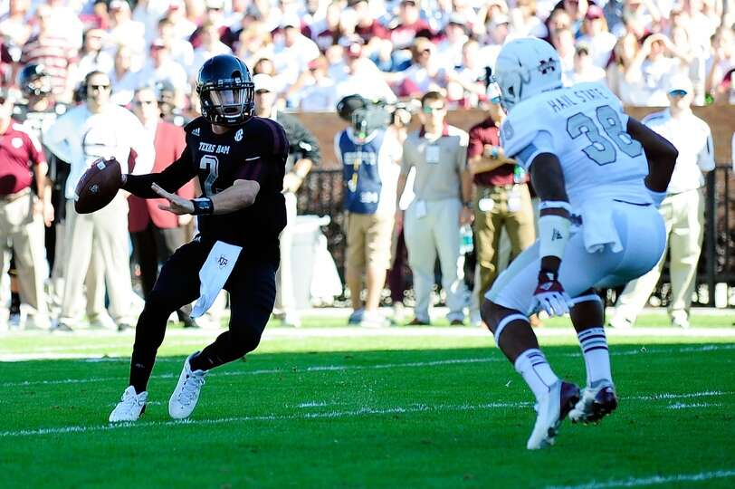 Johnny Manziel #2 of the Texas A&M Aggies is pressured by  Dee Arrington #38 of the Mississippi Stat