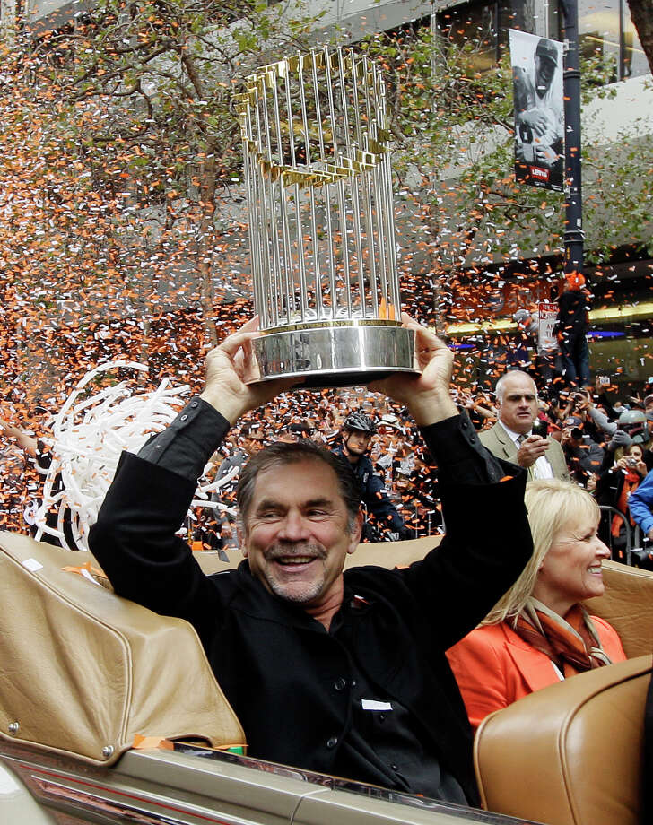 San Francisco Giants manager Bruce Bochy holds the World Series trophy as confetti falls during the baseball team's World Series victory parade, Wednesday, Oct. 31, 2012, in San Francisco. (AP Photo/Jeff Chiu) Photo: Jeff Chiu / AP