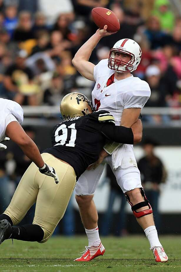 BOULDER, CO - NOVEMBER 03:  Quarterback Kevin Hogan #8 of the Stanford Cardinals delivers a pass as he is hit by defensive lineman Kirk Poston #91 of the Colorado Buffaloes at Folsom Field on November 3, 2012 in Boulder, Colorado.  (Photo by Doug Pensinger/Getty Images) Photo: Doug Pensinger, Getty Images