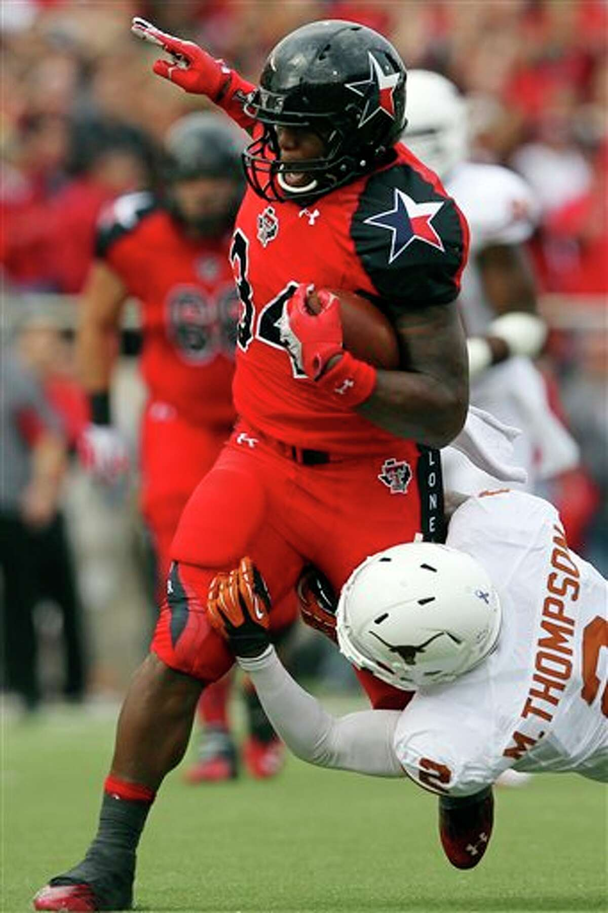 Texas Tech's Kenny Williams is hit by Texas' Mykkele Thompson during their NCAA college football game, Saturday, Nov. 3, 2012, in Lubbock, Texas. (AP Photo/Lubbock Avalanche-Journal,Stephen Spillman) LOCAL TV OUT