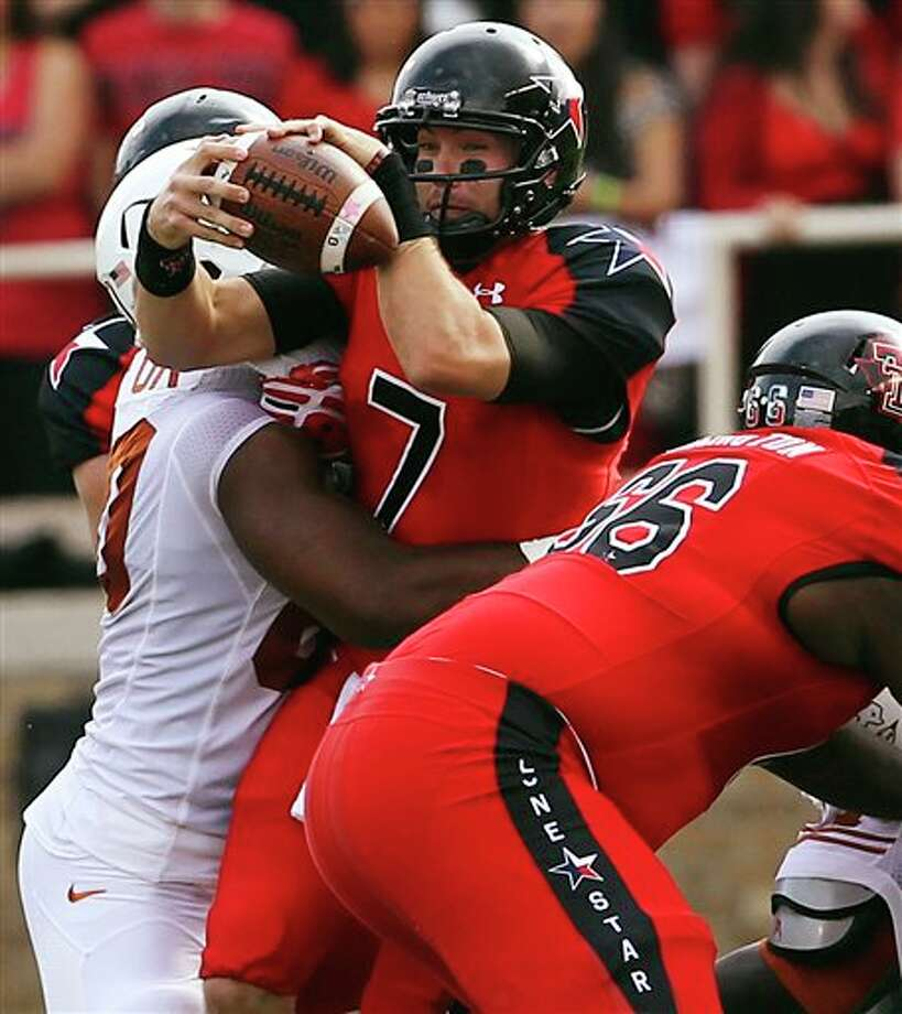 Texas Tech's Seth Doege is hit by Texas' Alex Okafor ahead of Texas Tech's Deveric Gallington (66) during their NCAA college football game, Saturday, Nov. 3, 2012, in Lubbock, Texas. (AP Photo/Lubbock Avalanche-Journal,Stephen Spillman)  LOCAL TV OUT Photo: Stephen Spillman, AP / The Avalanche-Journal