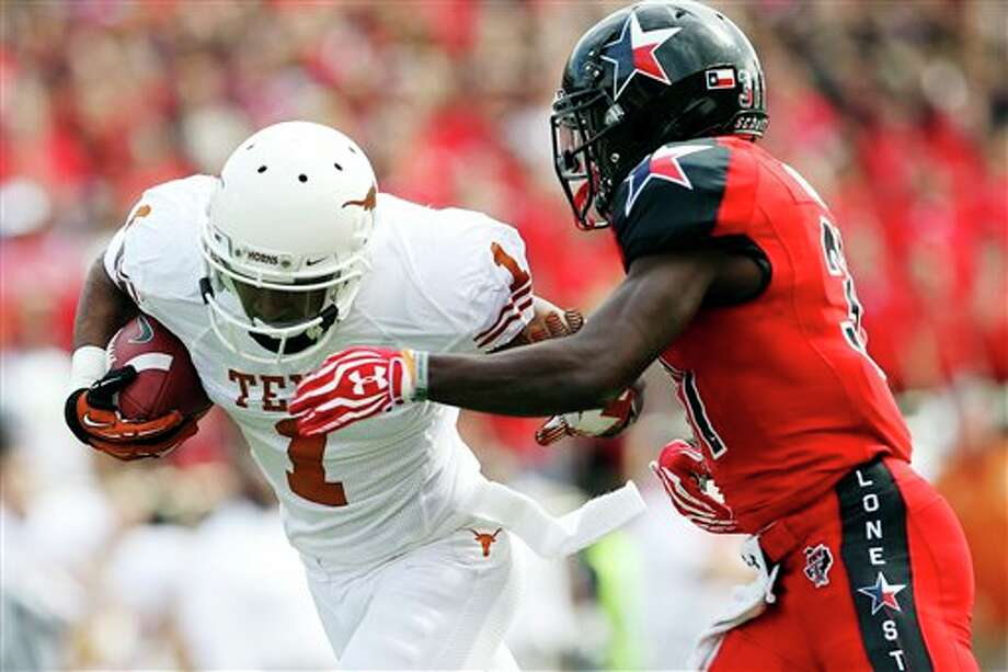 Texas' Mike Davis makes a catch ahead of Texas Tech's Eugene Neboh during their NCAA college football game, Saturday, Nov. 3, 2012, in Lubbock, Texas. (AP Photo/Lubbock Avalanche-Journal,Stephen Spillman)  LOCAL TV OUT Photo: Stephen Spillman, AP / The Avalanche-Journal
