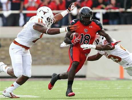 Texas Tech's Eric Ward is hit by Texas' Tevin Jackson (11) and Carrington Byndom (23) during their NCAA college football game, Saturday, Nov. 3, 2012, in Lubbock, Texas. (AP Photo/Lubbock Avalanche-Journal,Stephen Spillman)  LOCAL TV OUT Photo: Stephen Spillman, AP / The Avalanche-Journal