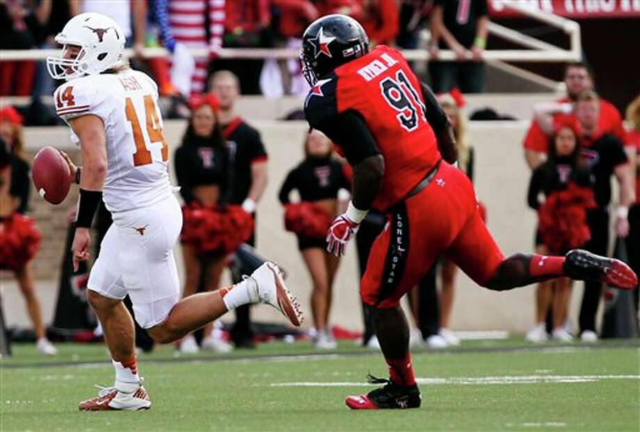 Texas' David Ash runs past Texas Tech's Kerry Hyder during their NCAA college football game, Saturday, Nov. 3, 2012, in Lubbock, Texas. (AP Photo/Lubbock Avalanche-Journal,Stephen Spillman)  LOCAL TV OUT Photo: Stephen Spillman, AP / The Avalanche-Journal