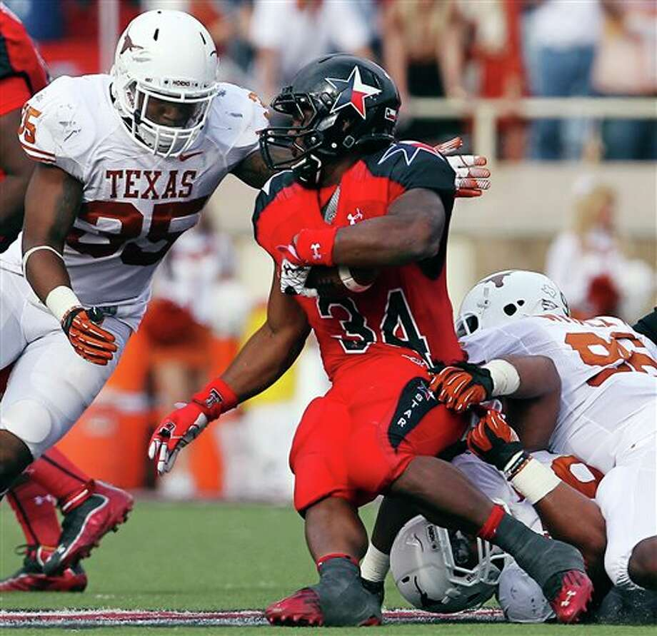 Texas Tech's Kenny Williams is taken down by Texas' Desmond Jackson, bottom, Chris Whaley (96) and Kendall Thompson (35) during their NCAA college football game, Saturday, Nov. 3, 2012, in Lubbock, Texas. (AP Photo/Lubbock Avalanche-Journal,Stephen Spillman)  LOCAL TV OUT Photo: Stephen Spillman, AP / The Avalanche-Journal