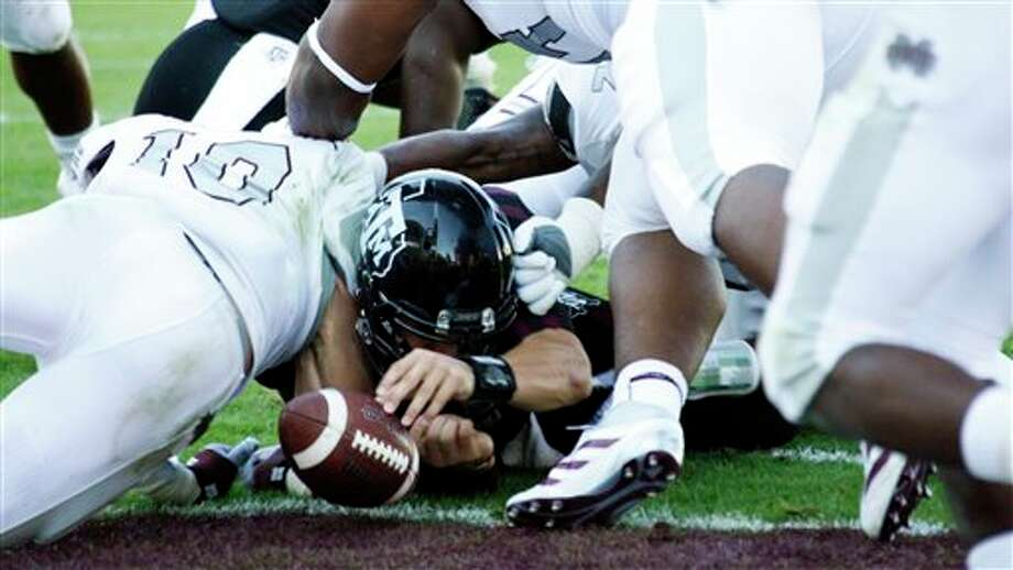 Texas A&M quarterback Johnny Manziel loses the ball as he tries for a 1-yard touchdown run in the third quarter as Mississippi State linebacker Cameron Lawrence (10) stops him in the third quarter of their NCAA college football game in Starkville, Miss., Saturday, Nov. 3, 2012. Manziel was credited with the fumble as Mississippi State recovered in the end zone for a touchback. Texas A&M won 38-13. (Rogelio V. Solis / Associated Press) Photo: Rogelio V. Solis, AP / AP