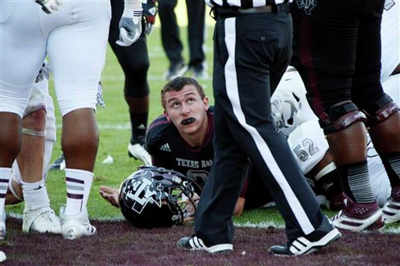 Texas A&M quarterback Johnny Manziel (2) looks up at the official to see if he is credited with a to