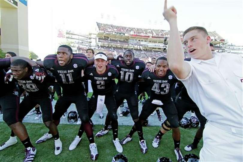 Texas A&M quarterback Johnny Manziel (2) joins teammates as they sing the school chant with a yell l