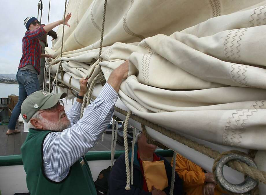 Stacey Fernandez and Tom Hunt lower a sail as the scow schooner Alma docks in S.F.'s India Basin. Photo: Paul Chinn, The Chronicle