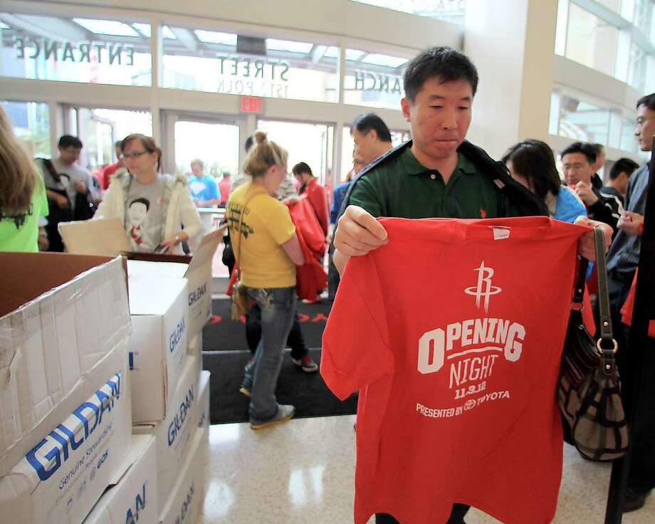 "Houston Rockets fans come through the doors as they are given ""opening night"" giveaway t-shirts before the start of the home opener NBA game at Toyota Center, Saturday, Nov. 3, 2012, in Houston. Photo: Karen Warren, Houston Chronicle / © 2012  Houston Chronicle"