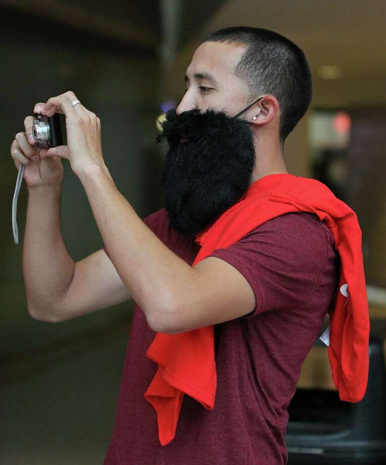 "John Martinez takes photos wearing ""the beard"" before the start of the home opener NBA game at Toyota Center, Saturday, Nov. 3, 2012, in Houston. Photo: Karen Warren, Houston Chronicle / © 2012  Houston Chronicle"