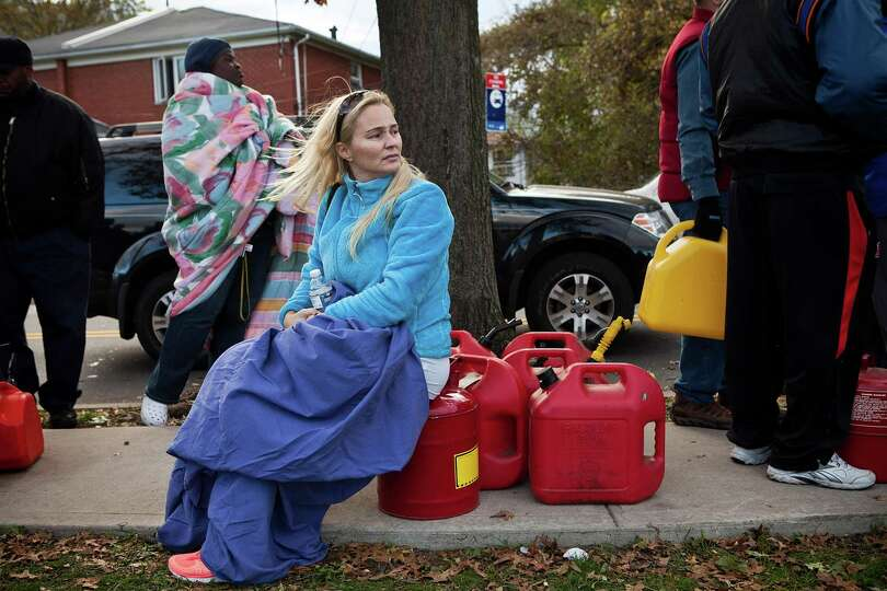 Michele Connolly waits in line for free gasoline distributed by the National Guard at the Armory on