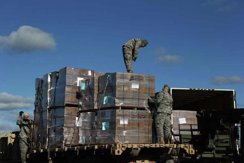U.S. Army soldiers secure portable meals from the Federal Emergency Management Agency (FEMA) onto de