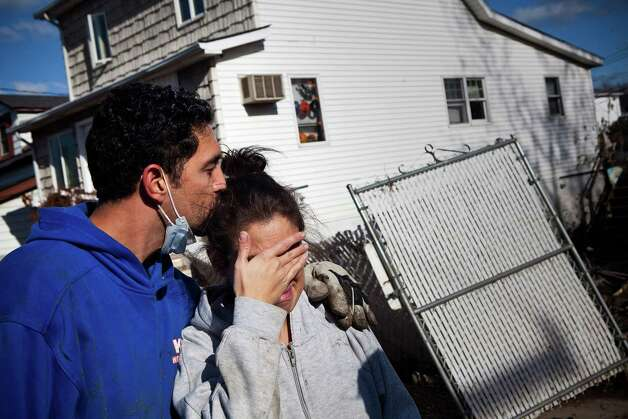 Doctor Howard Goldsmith consoles his wife, Doctor Rosanna Troia while helping clean out Troia's mother's home in the Midland Beach neighborhood of Staten Island on November 3, 2012 in New York City. As clean up efforts from Superstorm Sandy continue, colder weather and another storm predicted for next week are beginning to make some worried. Photo: Andrew Burton, Getty Images / 2012 Getty Images