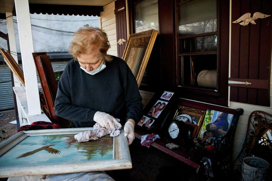 Angela Troia wipes off a painting damaged by Superstorm Sandy in the Midland Beach neighborhood of Staten Island on November 3, 2012 in New York City. As clean up efforts from Superstorm Sandy continue, colder weather and another storm predicted for next week are beginning to make some worried. Photo: Andrew Burton, Getty Images / 2012 Getty Images
