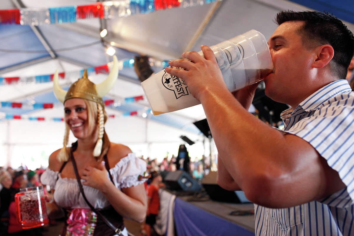 Cheyenne Hodges, left, and Michael Tashnick, both of Austin, drink and dance by the stage as the Alex Meixner Band plays during Wurstfest in New Braunfels on Saturday, Nov. 3, 2012.
