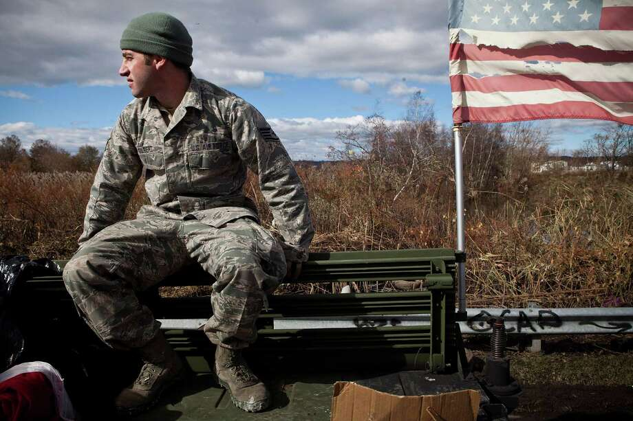 Members of the US Air Force National Guard patrol the Midland Beach neighborhood of Staten Island, looking for those in need of food, water or clothing, on November 3, 2012 in New York City. As clean up efforts from Superstorm Sandy continue, colder weather and another storm predicted for next week are beginning to make some worried. Photo: Andrew Burton, Getty Images / 2012 Getty Images