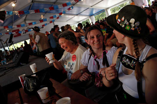 Kathy Rubey, of New Ulm, MN, from left, Jamie Logsdon and Whitney Welsch, both of Austin, join arms to sway back and forth together as the Alex Meixner Band plays during Wurstfest in New Braunfels on Saturday, Nov. 3, 2012. Photo: Lisa Krantz, San Antonio Express-News / © 2012 San Antonio Express-News