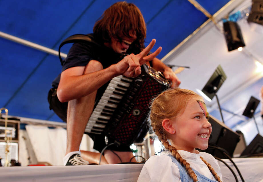 Alex Meixner, of the Alex Meixner Band, gets in on a photograph being taken of Riley Patton, 6, of Huffman, in front of the stage he is performing on last week during Wurstfest. Photo: Lisa Krantz, San Antonio Express-News / © 2012 San Antonio Express-News