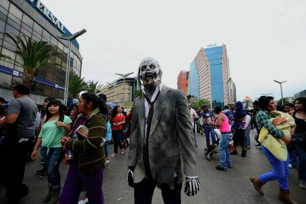 "A man dressed up as a zombie takes part in a ""Zombie Walk"" at the Revolution Monument in Mexico City on November 3, 2012. According to organizers, 15,000 people will take part in the event in an attempt to set a new Guinness record.  AFP PHOTO/Alfredo EstrellaALFREDO ESTRELLA/AFP/Getty Images Photo: ALFREDO ESTRELLA, AFP/Getty Images / AFP"
