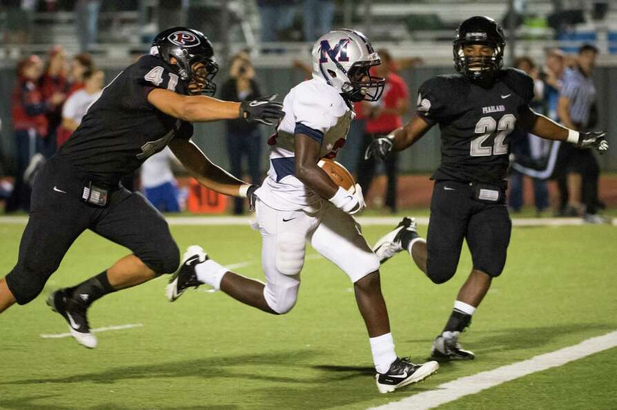 Manvel's Qyalan Clay (21) runs for a touchdown past Pearland defensive end Deonte Givens (41) and de