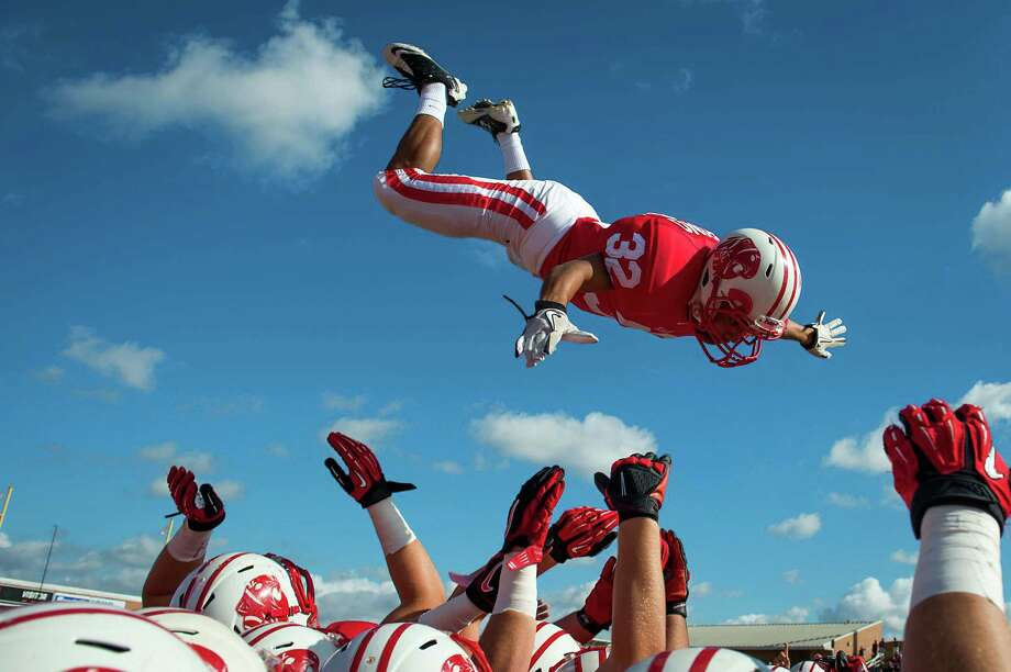 Katy defensive back Juan Yeverino is tossed high in the air over his teammates as they take the field before a high school football game against Cinco Ranch at Rhodes Stadium on Saturday, Nov. 3, 2012, in Katy. Photo: Smiley N. Pool, Houston Chronicle / © 2012  Houston Chronicle