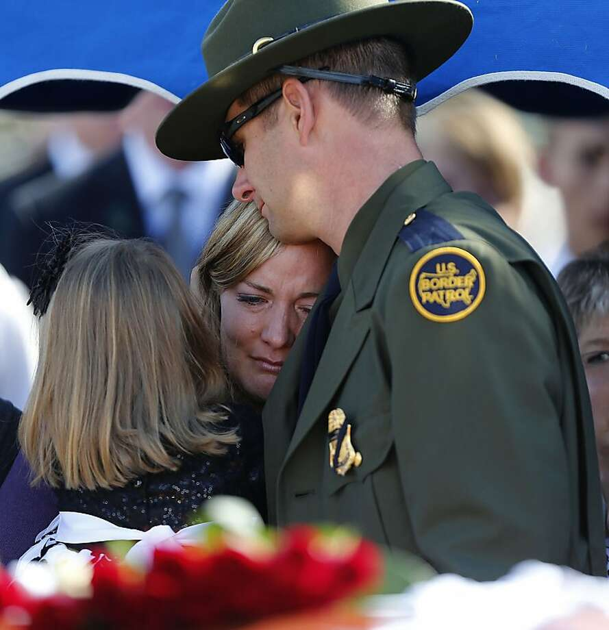 The wife and brother of Border Patrol Agent Nicholas Ivie, Christy (center) and Joel, hug at his funeral in Utah last month. Nicholas Ivie was killed in what the FBI has called friendly fire. Photo: George Frey, Getty Images