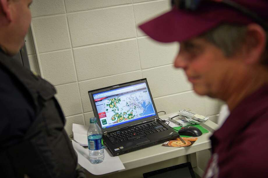 Officials keep an eye on weather radar after lightening detected in the area forced a delay in during in a high school football game between Cinco Ranch and Katy at Rhodes Stadium on Saturday, Nov. 3, 2012, in Katy. Photo: Smiley N. Pool, Houston Chronicle / © 2012  Houston Chronicle