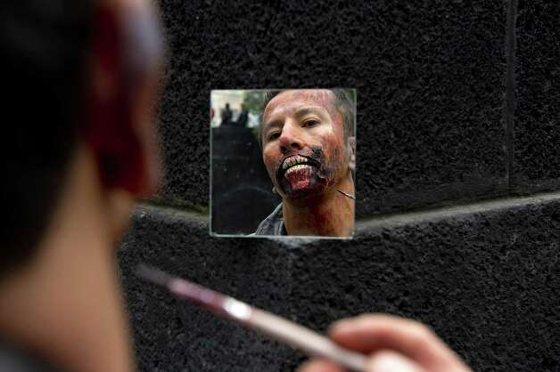 "A man puts the final touches to his zombie make up to take part in a ""Zombie Walk"" at the Revolution Monument in Mexico City on November 3, 2012. According to the organization, 15,000 people will take part in the event in an attempt to set a new Guinness record. Photo: YURI CORTEZ, AFP/Getty Images / YURI CORTEZ"